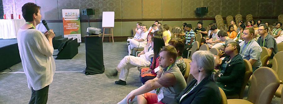 Cora Halder in einem Saal vor Zuhörern, unter ihnen zahlreiche mit Down-Syndrom