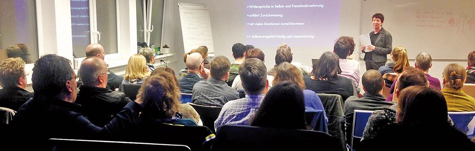Cora Halder referiert vor einer Gruppe von Zuhörern in einem Seminarraum